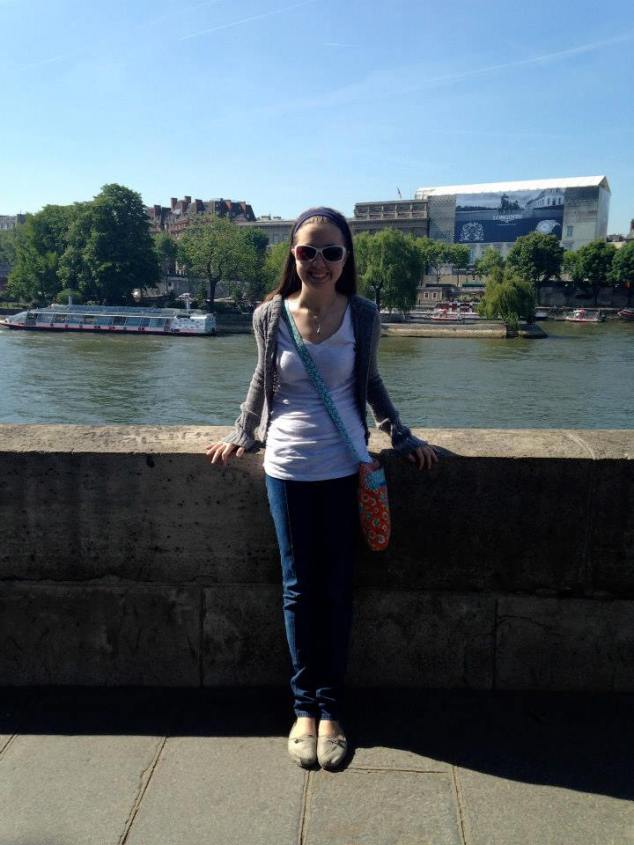 "On the Seine in Paris in my ""uniform:"" Jeans, t-shirt, sweater, walking shoes, crossbody bag."