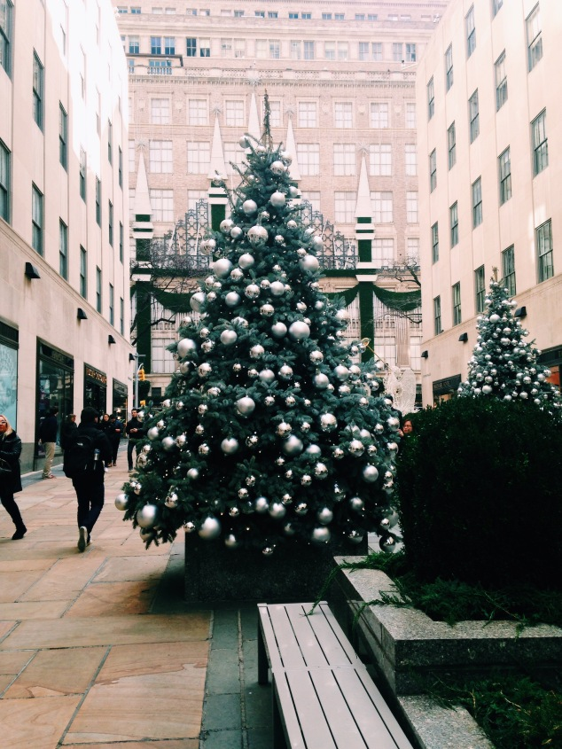 Christmas trees on Rockefeller Plaza with Saks Fifth Avenue in the background